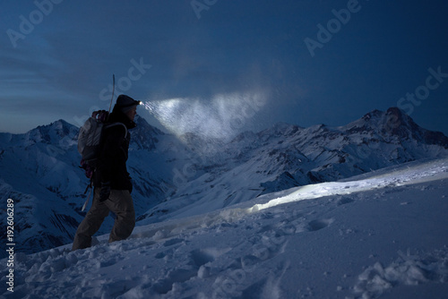 Obraz Brave night explorer climbs on high snowy mountains and lights the way with a headlamp. Extreme expedition. Ski tour. Snowboarder commit climb on winter slope. Backcountry - fototapety do salonu