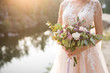 canvas print picture - The bride in a beige wedding dress holding a lush bridal bouquet of lilac roses and a lot of greenery. Stylish wedding bouquet on the sunset background