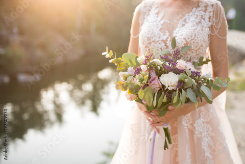 Cuadros en Lienzo The bride in a beige wedding dress holding a lush bridal bouquet of lilac roses and a lot of greenery