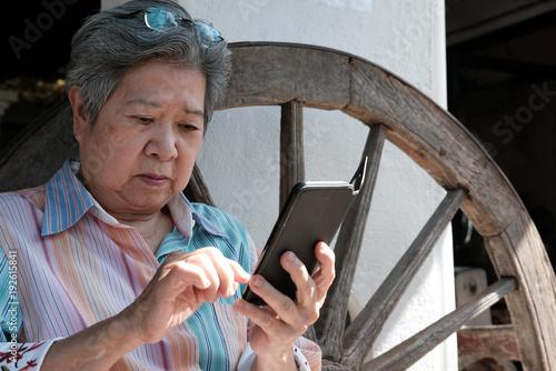Poster  elder woman holding mobile phone in garden