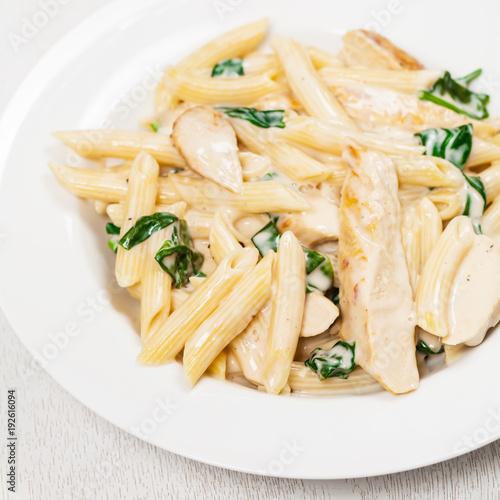 Photo Spinach Chicken Alfredo Parmesan Pasta. Selective focus.