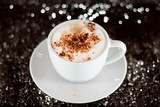 cappuccino on a black surface with bokeh