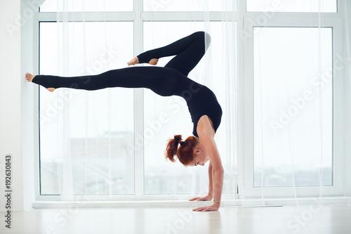 Valokuvatapetti Beautiful sporty fit yogi woman practices yoga handstand asana Bhuja Vrischikasana - Scorpion handstand pose at the yoga studio