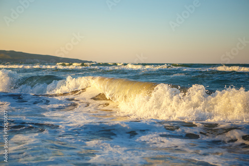 Spoed Foto op Canvas Noordzee waves in the sunset. beautiful sea with waves and spray, the concept of journey, a beautiful beach card. sea waves at sunset, in summer