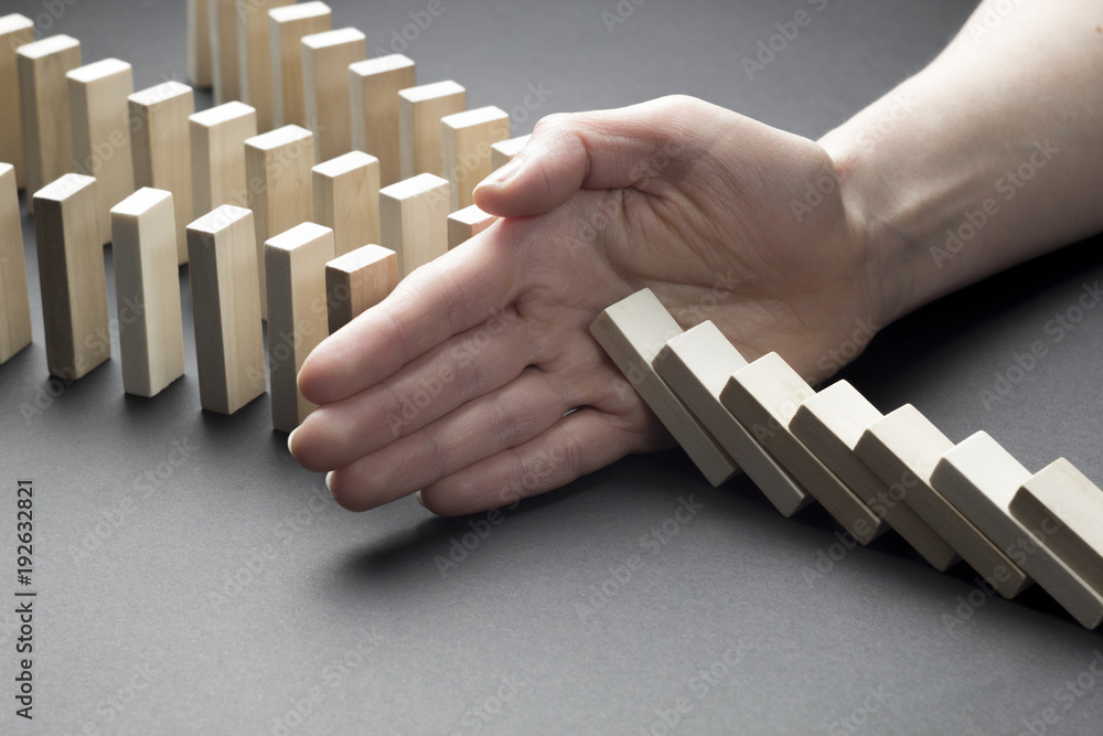 Fototapeta The financial crisis and economic decline. Businessman hand stop domino continuous tipping or risk.