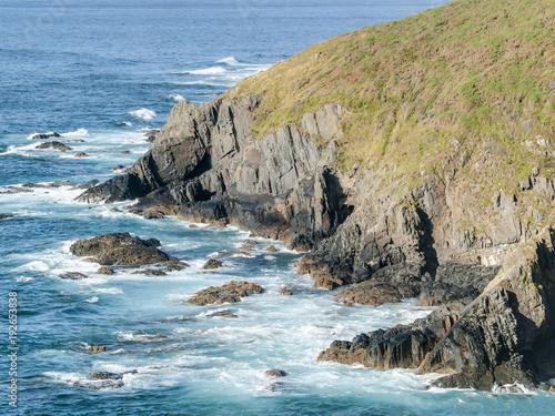 Costa escarpada de roca, aguas turquesas y espuma del mar