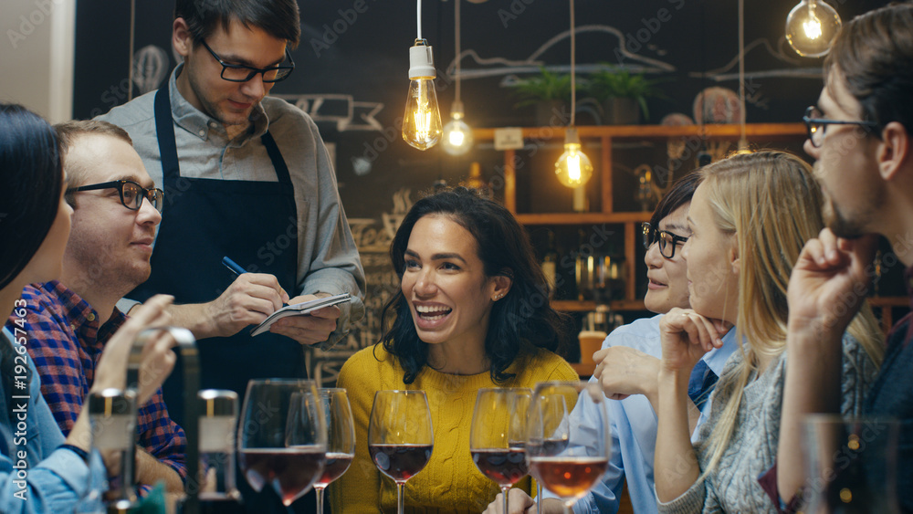 Fototapety, obrazy: In the Bar/ Restaurant Waiter Takes Order From a Diverse Group of Friends. Beautiful People Drink Wine and Have Good Time in this Stylish Place.