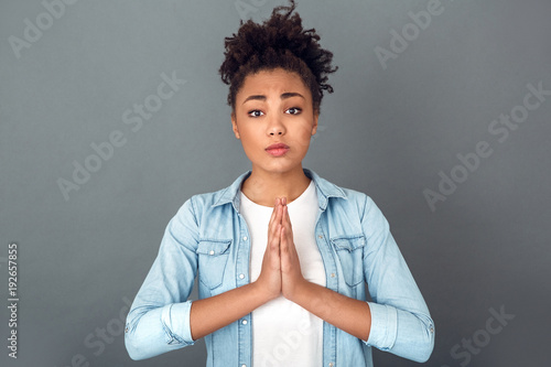 Young african woman isolated on grey wall studio casual daily lifestyle praying Fototapeta