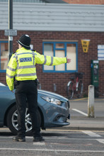 Policeman Directing And Managing Traffic On Busy Road