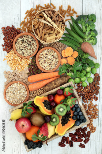 Health food for a high fibre diet with whole wheat pasta, grains, legumes, nuts, fruit, vegetables and cereals with foods high in omega 3, antioxidants and vitamins. Rustic background top view.