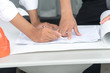 Closeup of a person's hands pointing on blue print. Hands of two construction engineers work on blue print.