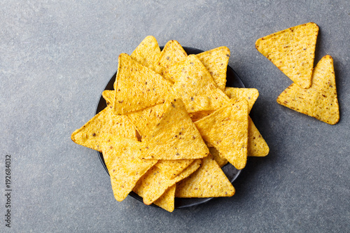 Nachos chips in bowl. Stone background. Top view.