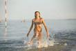 water fun. the girl runs along the seashore.