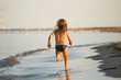 water fun. the girl runs along the seashore.