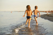 Girl and boy are running along the sea shore