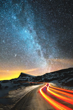 Night Landscape. Night Sky With A North Hemisphere Milky Way And Stars. The Night Road Illuminated By The Car Winds With A Serpentine And Leaves In A Distance To A Foot Of An Acute Rock. Light Trails