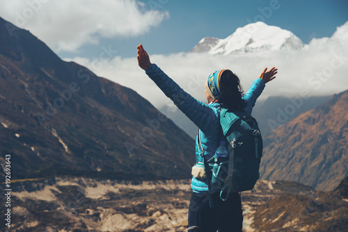 Fototapeta Standing young woman with backpack and raised up arms on the hill and looking on mountains. Landscape with happy girl, mountains, blue sky with clouds in autumn in Nepal. Travel. Trekking. Vintage obraz