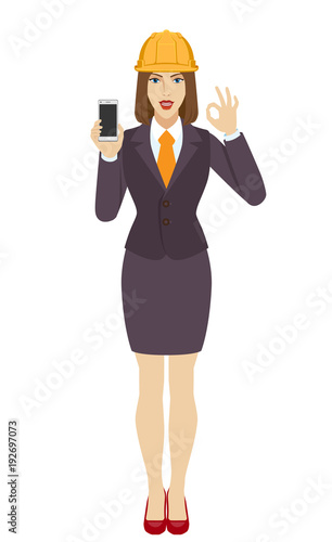 Businesswoman in construction helmet holding a mobile phone and  show a okay han Canvas Print