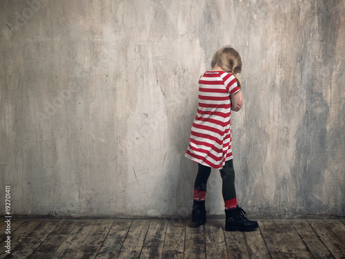 Valokuva  A punished child standing by the wall.