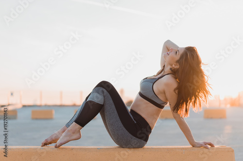 Sporty young woman on wall