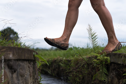 Caucasian woman step over the water ditch Poster