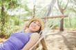 Romantic hipster woman lying and resting on a hammock in forest