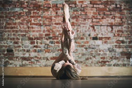 Beautiful young woman practices yoga asana Prasarita Padasana at the yoga studio on a brick wall background Canvas Print