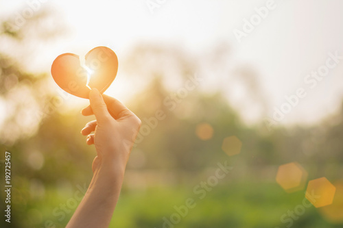 Silhouette broken heart,close up woman hand holding broken heart in the park Wallpaper Mural