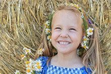 A Laughing 3 Years Old Girl With Chamomile Wreath Is Standing In Front Of A Straw Ball