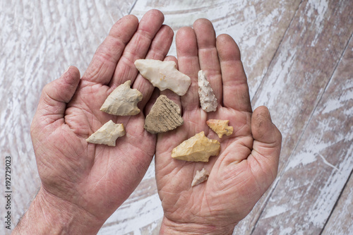 Hands Holding Arrowheads and Pottery