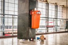 Orange Plastic Garbage Can With Overflow Junk And Litter On The Ground Polluting Indoor Space Of The Building