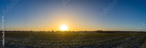 Foto auf Gartenposter Landschappen Panorama eines Sonnenaufgangs hinter einem Feld, leicht mit Schnee bedeckt