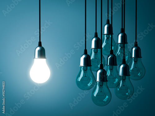 Fotografie, Obraz One hanging light bulb glowing and standing out from unlit incandescent bulbs on dark green pastel color background
