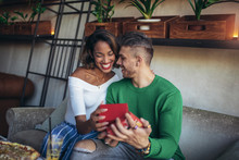 Happy  Interracial Couple Sitting In Cafe Bar. Man Giving Gift To His Girlfriend.