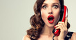 Beautiful woman in pin up style with vintage red phone.  Shocked pretty girl  . Presenting your product. Expressive facial expressions