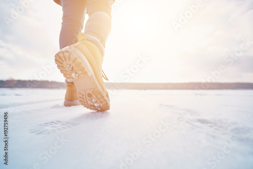 Fototapeta tourist walking away. tourist in boots goes into the distance through the snow in the sunset low angle obraz