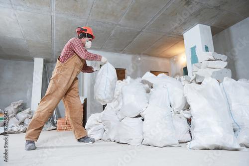 Fotografía  Worker collecting construction waste in bag