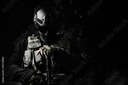 Fotografía  Black and white swat soldier posing with dissolving effect on black background