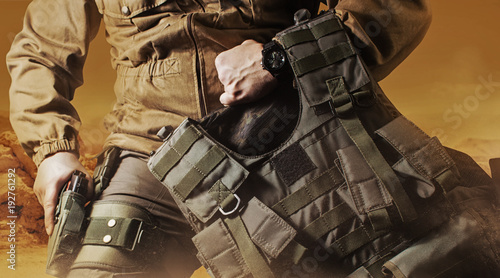 Fotografía  Photo of a soldier in military outfit holding a gun and bulletproof vest on orange desert background