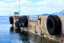 Old Deserted Ferry Dock In Norway. With Big Tires For Protection Of Ship.