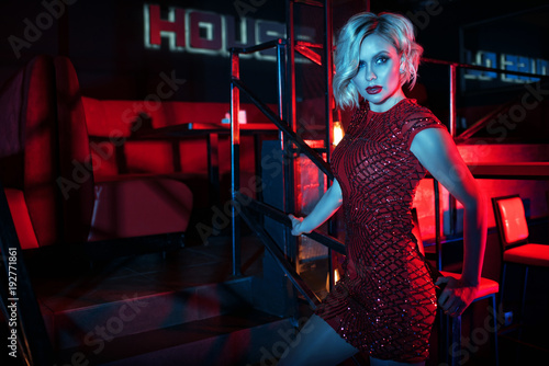Beautiful glam blond woman with provocative make up wearing red short fitted sequin dress standing on the stairs in the night club in colourful neon lights. Club interior on background. Text space