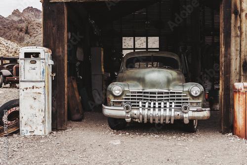 Stary samochód zardzewiały rocznika opuszczony w opuszczonej stacji benzynowej.