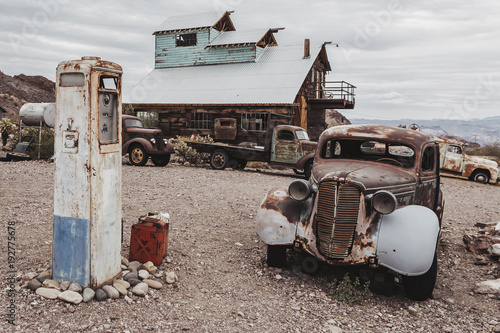 Old vintage rusty car truck abandoned near old fuel pump in the desert