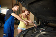 Mechanic shows a young female how to use a wrench to repair a car