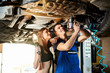 Mechanic tightens the bolts of the bottom of the car, the girl helps him with lightning