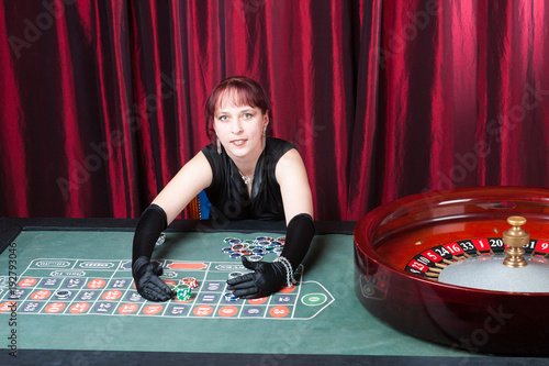 ludomania, girl wearing  black gloves and black dress parlays in a casino Obraz na płótnie
