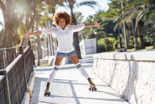 Black Woman, Afro Hairstyle, On Roller Skates Riding Near The Beach.
