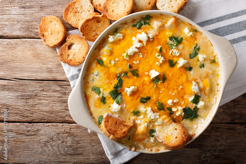 American food: hot chicken buffalo dip close-up in a baking dish with toasted bread. Horizontal top view