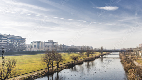 Blue river plain on a green nature park on Lleida city, with architectural details on a the skyline and solid blue sunny sky background