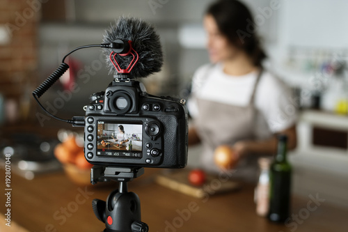Fotografie, Obraz  Female vlogger recording cooking related broadcast at home
